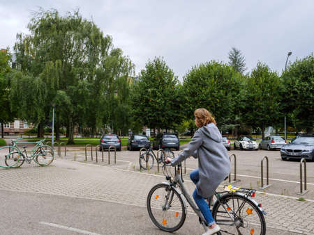 Side view of young woman driving a bike in central Strasbourg in Place de lUniversite Éditoriale