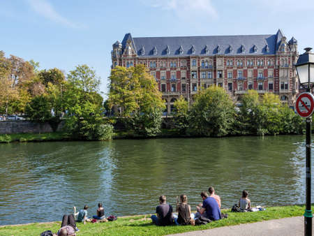 People sunbathing on the border of Ill river with Crous de Strasbourg