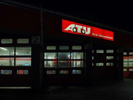 Car service store ATU Auto-Teile-Unger at night with illuminated signage