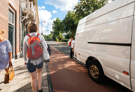 Woman walks on Dutch street near delivery man with parcels