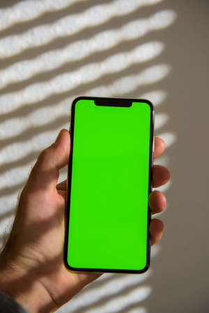 Male hand holding new smartphone telephone with green screen and stripped from sunrays background