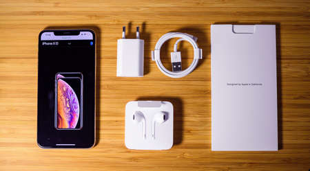 View from above at latest Apple Computers iPhone XS gold color 256GB smartphone featuring all contents of the package - wooden table background