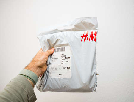 olding H and M white plastic parcel Hennes and Mauritz AB