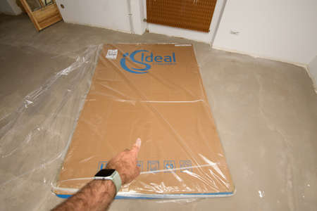 pointing to large cardboard box protected by plastic foil with logotype of Ideal Standard stone resin shower tray