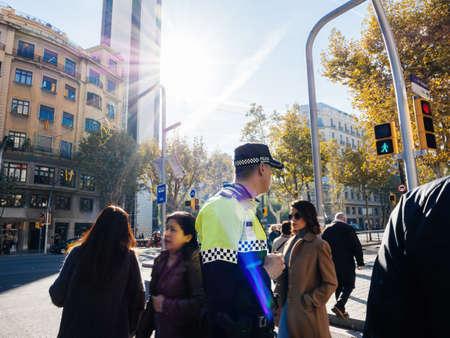 Policia, Guardia Urbana officer surveillance of city streets surveilling the pedestrians