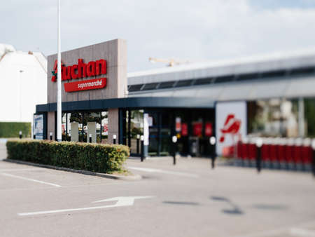 Closed Auchan supermarket store with empty parked during COVID-19