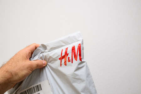 Close-up macro detail of male hand holding H and M white plastic parcel Éditoriale