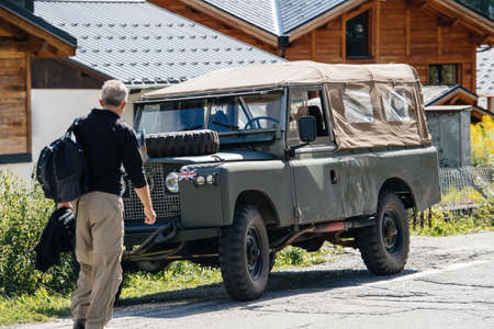 Rear view of adventure tourist man walking toward to Land Rover Defender SUV