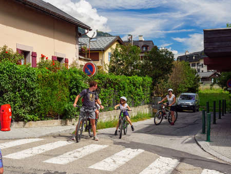 Family, mother father and daughter on bikes discovering the iconic village of Chamonix
