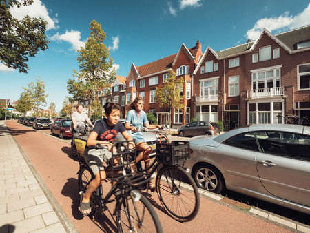 Adult women and young boy people riding bikes on Haarlem street fast commuting on Dutch street Éditoriale