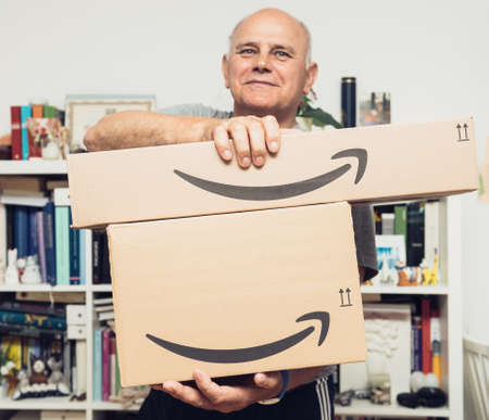 Senior man smiling while holding two new Amazon Prime parcel logotype with the smiling arrow - the internet conglomerate founded by Jeff Bezos founding Amazon in a home garage in 1994