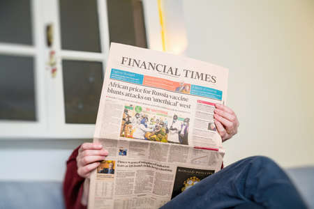 Woman reading in living room the latest Financial Times Business Banque d'images - 167821605