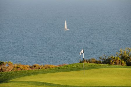 A golf course hole close to the water with a sailboat in the distance.  Stock Photo