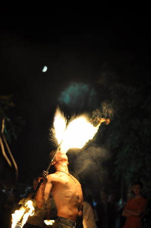 spitting: Man spitting fire at a carnaval Stock Photo
