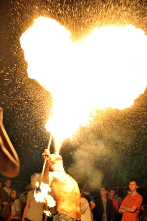 spitting: Man spitting fire that shapes like a hart