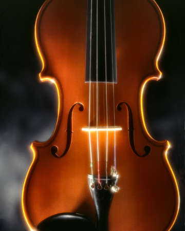 violin top-plate enlightened by a magic light in front of a dark fog