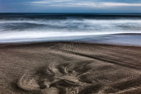 primordial footprint on the sand in front of the sea Imagens