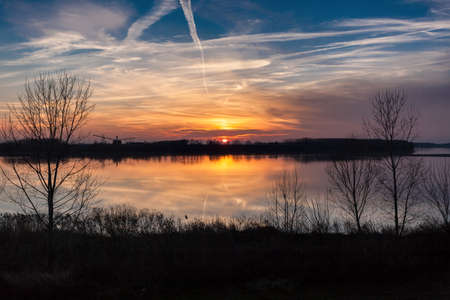 Sun setting over the river seen from the banks Stock Photo