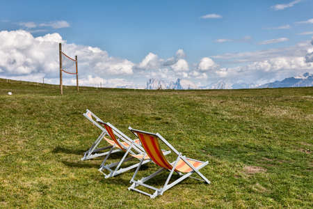 Deck chairs on a mountain meadow in the background of the Dolomites