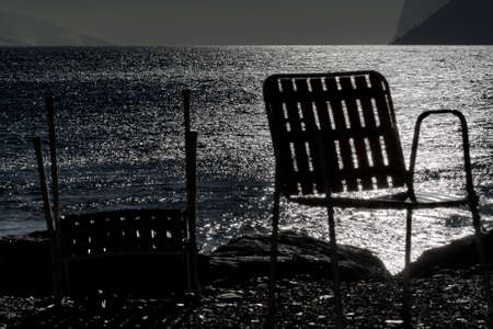 Chairs in silhouette on the shore of the lake