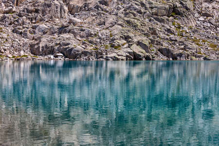 reflections of the rocks on the turquoise high mountain lake
