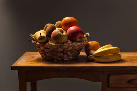 basket of fruit on a wooden table with apples banana pears and kiwi