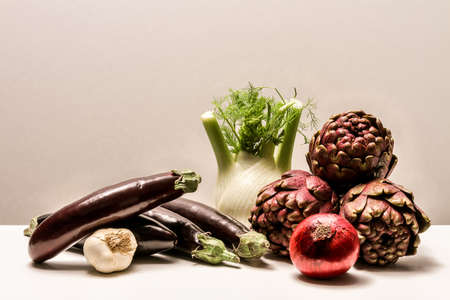 composition of various fresh vegetables with artichokes, aubergines, onions, garlic and fennel