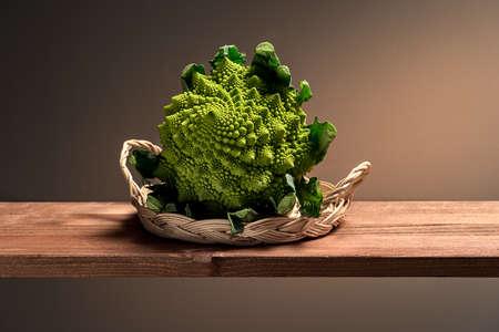 green cauliflower in a wicker basket on a wooden board
