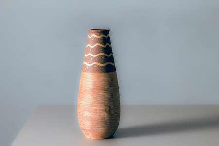 terracotta pot on gray shelf and grey background