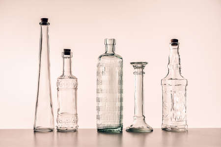 glass bottles of various shapes on a light background