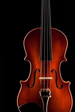wooden violin on a black background lit by side light