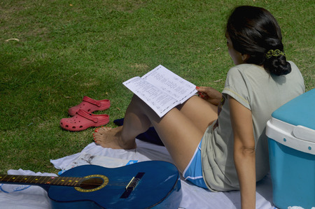 songbook: Relaxed woman rests at the campsite while studying a songbook
