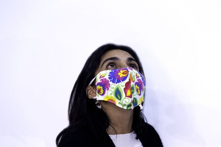 Young woman poses cheerfully with her chinstrap or mask. Positive attitude towards the coronavirus COVID 19 pandemic Фото со стока