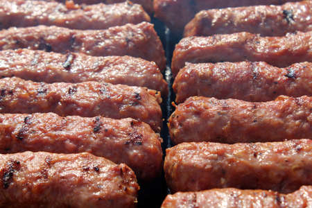 Grilled meat rolls, Mici or Mititei, traditional fresh Romanian bbq grill food cooked on the barbeque outside in the nature