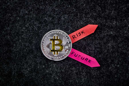 Cryptocurrency physical silver bitcoin coin with two colorful arrows.