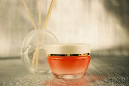 Body care concept. Skin cream in orange glass container Stock Photo