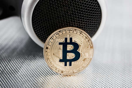 Cryptocurrency physical gold bitcoin coin near hairdryer.