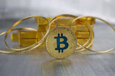 Cryptocurrency physical gold bitcoin coin near gold and rings. Редакционное