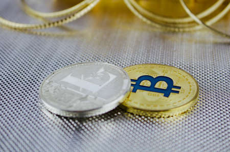 Digital currency physical silver litecoin coin and gold bitcoin coin on the silver background.