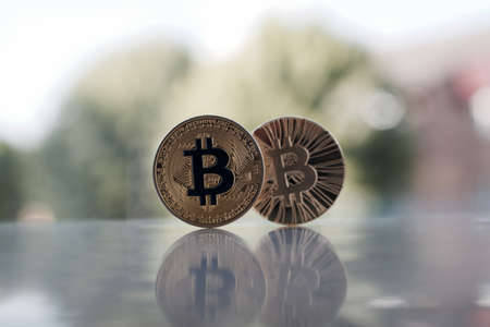 Digital currency two physical gold bitcoin coins on the table near the window. Editorial