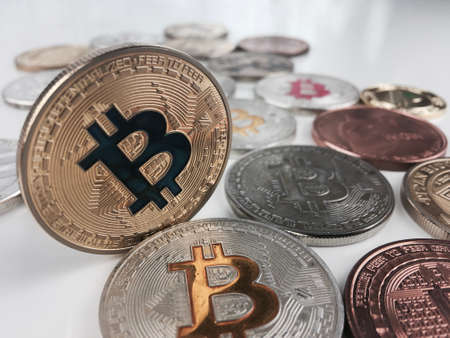 Cryptocurrency physical silver and gold bitcoin coins on the table. Фото со стока