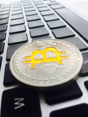 Cryptocurrency physical silver bitcoin coin on black computer keyboard. Zdjęcie Seryjne