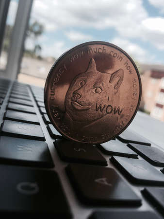 Digital currency physical brass dogecoin coin on the black computer keyboard near window. Stock Photo