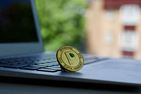 Cryptocurrency physical gold peercoin coin on the black computer keyboard.
