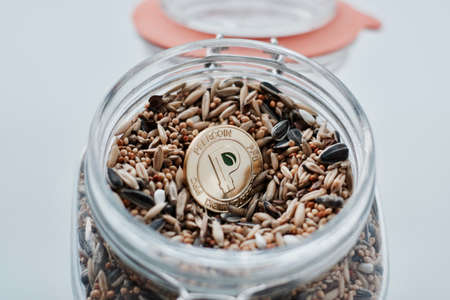 Cryptocurrency physical gold peercoin coin and seeds in glass jar.
