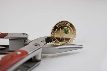 Digital currency physical gold peercoin coin and pocket knife on the table.