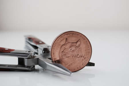 Digital currency physical brass dogecoin coin and silver pocket knife. Stock Photo