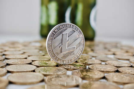 Digital currency physical silver litecoin coin on the money near green bottles.