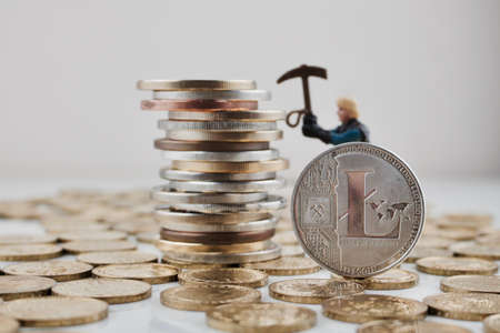 Digital currency physical silver Litecoin coin on the money near miner. Stock Photo