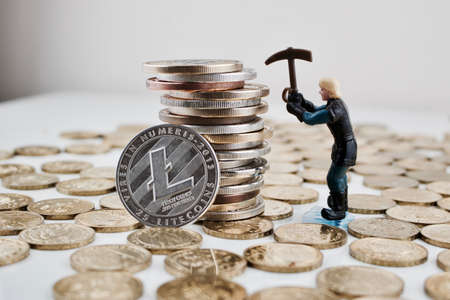 Cryptocurrency physical silver litecoin coin near money and miner. Litecoin mining.